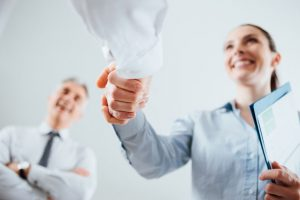 42512094 - confident business people shaking hands and woman smiling, recruitment and agreement concept